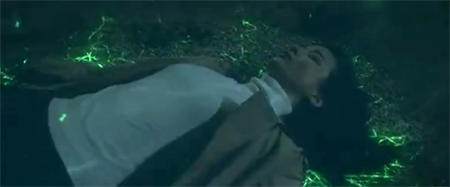 Soo Hyun lays on the lake floor while her surroundings start to glow green.