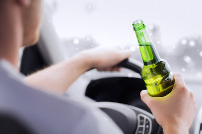 Man drink driving with bottle of beer in his hand