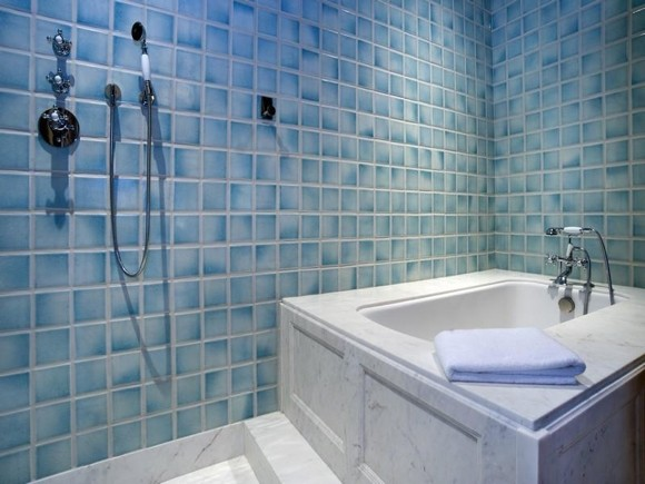 Photo of square bathtub and blue tiles in the bathroom