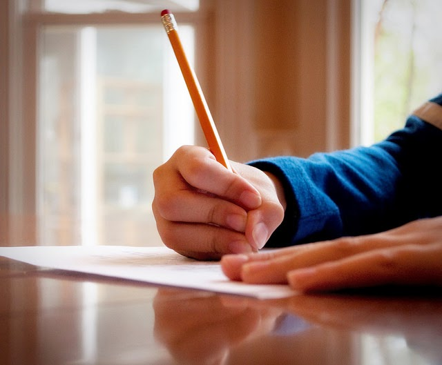 picture of a child writing on paper with a pencil
