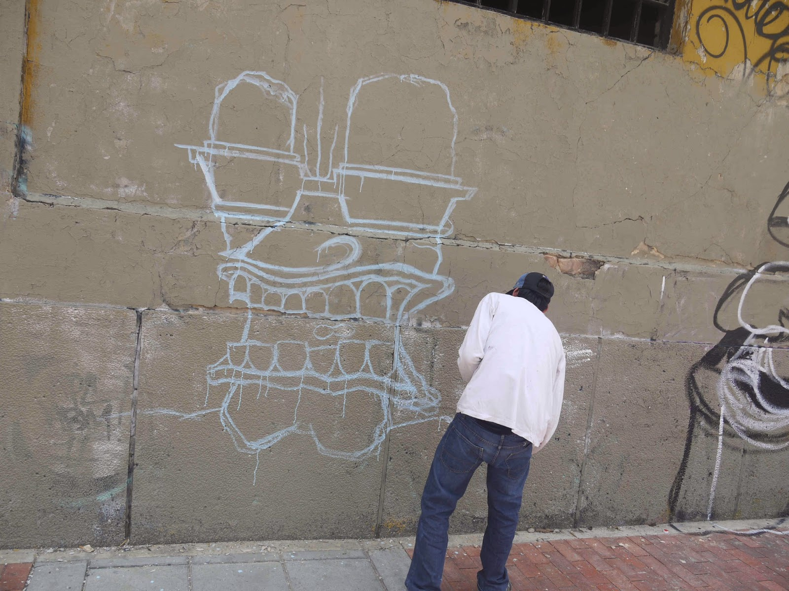 A graffiti artist sits on calle 26 above graffiti calling bogotás temporary designated mayor rafael pardo illegitimate