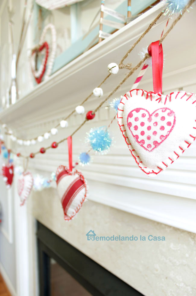 red and white fabric hearts hanging on beaded garland on Valentine mantel.
