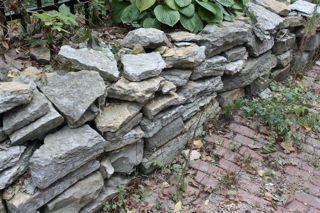 photo of fieldstone wall on a brick alleyway