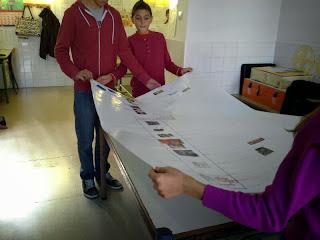 Varios alumnos miran el trabajo realizado en el mural sobre la línea del tiempo