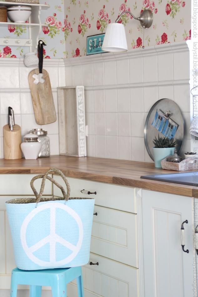 Hellblaue Korbtasche Peace auf türkisem Hocker vor der Küchenzeile mit Deko