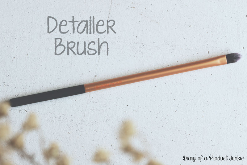 makeup brush on a white wooden plank with dried flowers