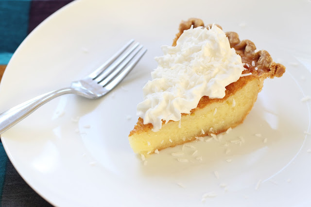 Shredded coconut & whipped cream atop a slice of buttermilk chess pie