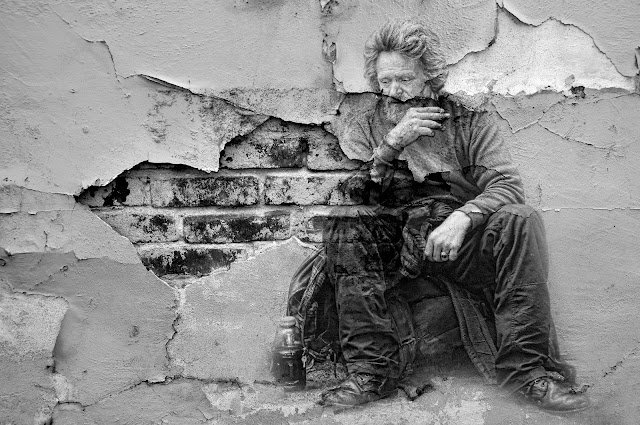 black and white photo collage of homeless man and broken brick wall