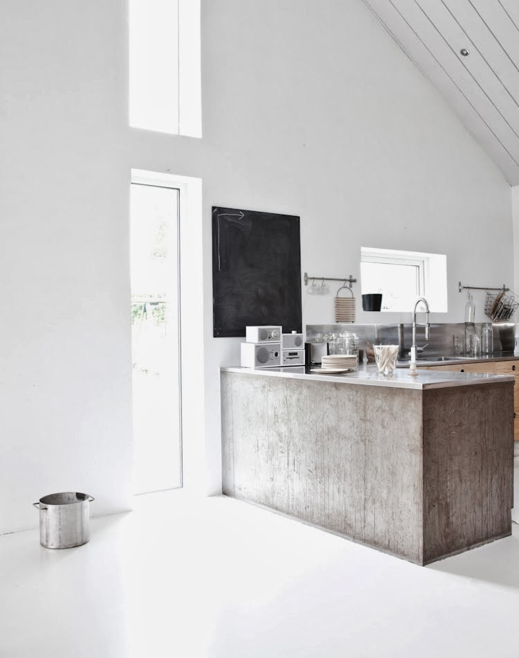 Minimalist kitchen with stainless counter tops and a black board