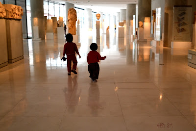 My girls alone in the Hellenistic/Roman hall of the New Acropolis Museum - In the distance Praxiteles' huge head of Artemis