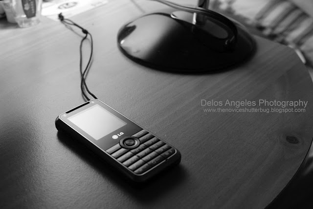 a black & white photo of my phone and desk