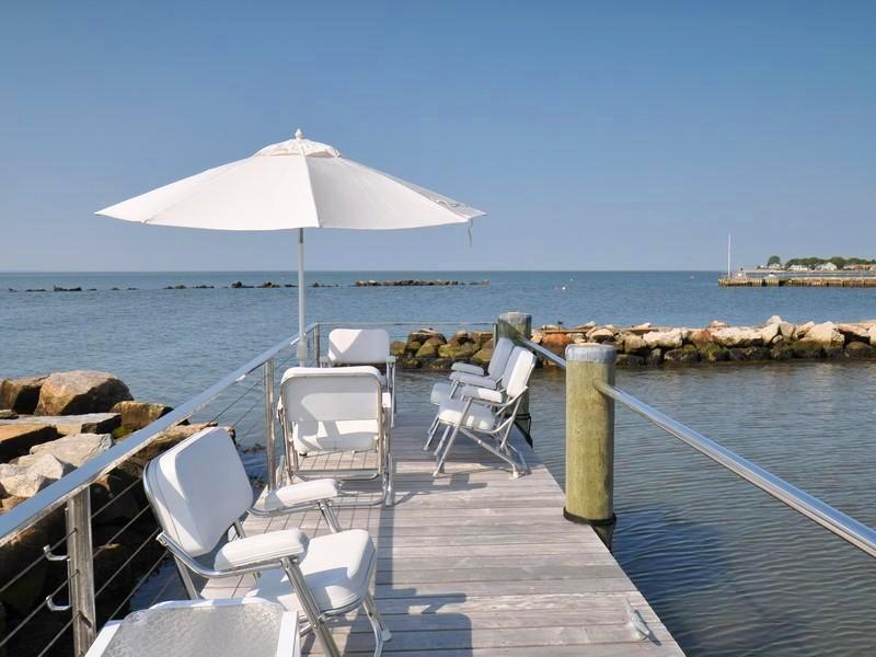 Private dock with metal chairs with white cushions and a large white umbrella