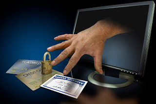 Illustration of identity theft, with hand coming out of a computer to steal credit and social security cards.