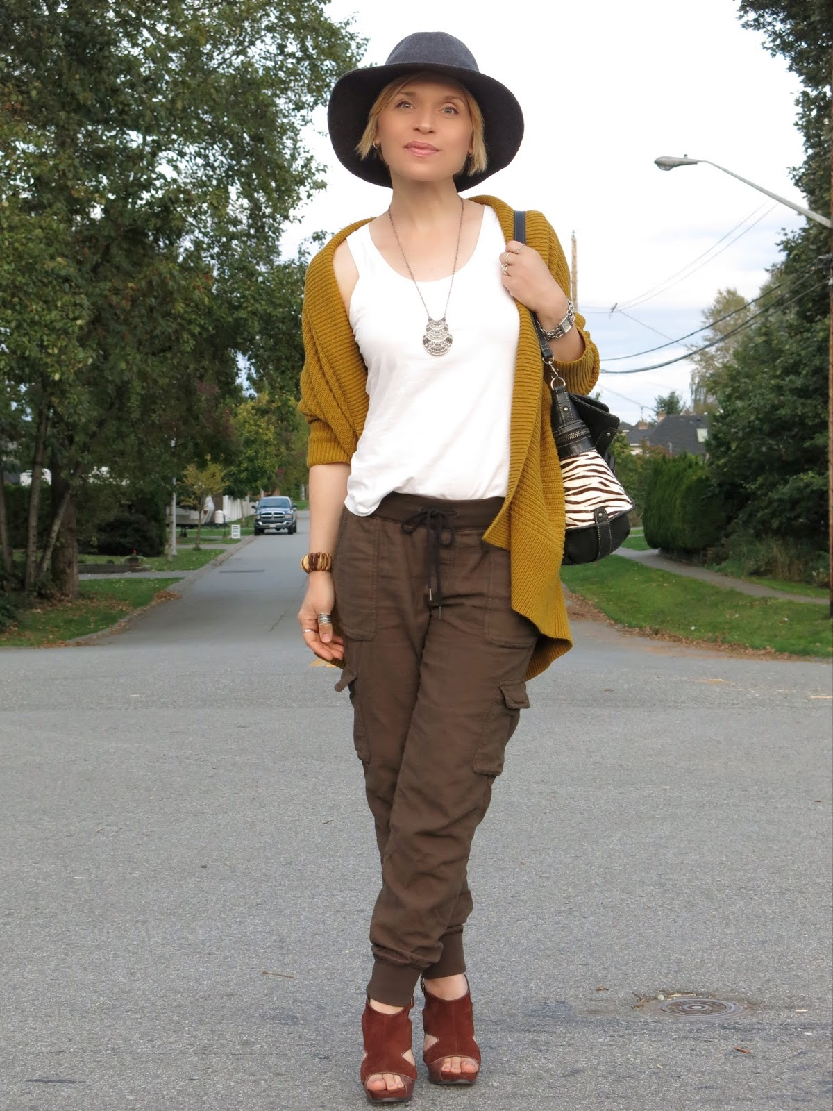 styling slouchy cargos with a drapey mustard-yellow cardigan, Nine West heels, and a floppy hat