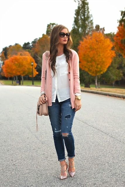 For All Things Lovely in a pink cardigan over a white blouse and distressed denim