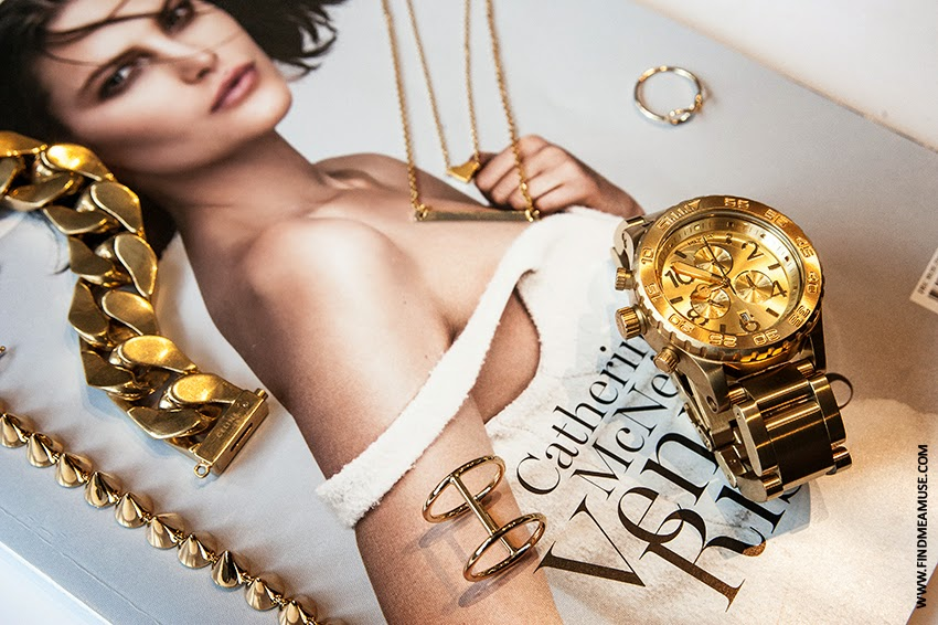 Flat lay set by Mandi - Find Me A Muse - including Celine gold cuban link bracelet, Nixon gold chrono watch, Jolie & Deen gold necklace and rings, Eddie Borgo gold spiked bracelet, RUSSH magazine backdrop