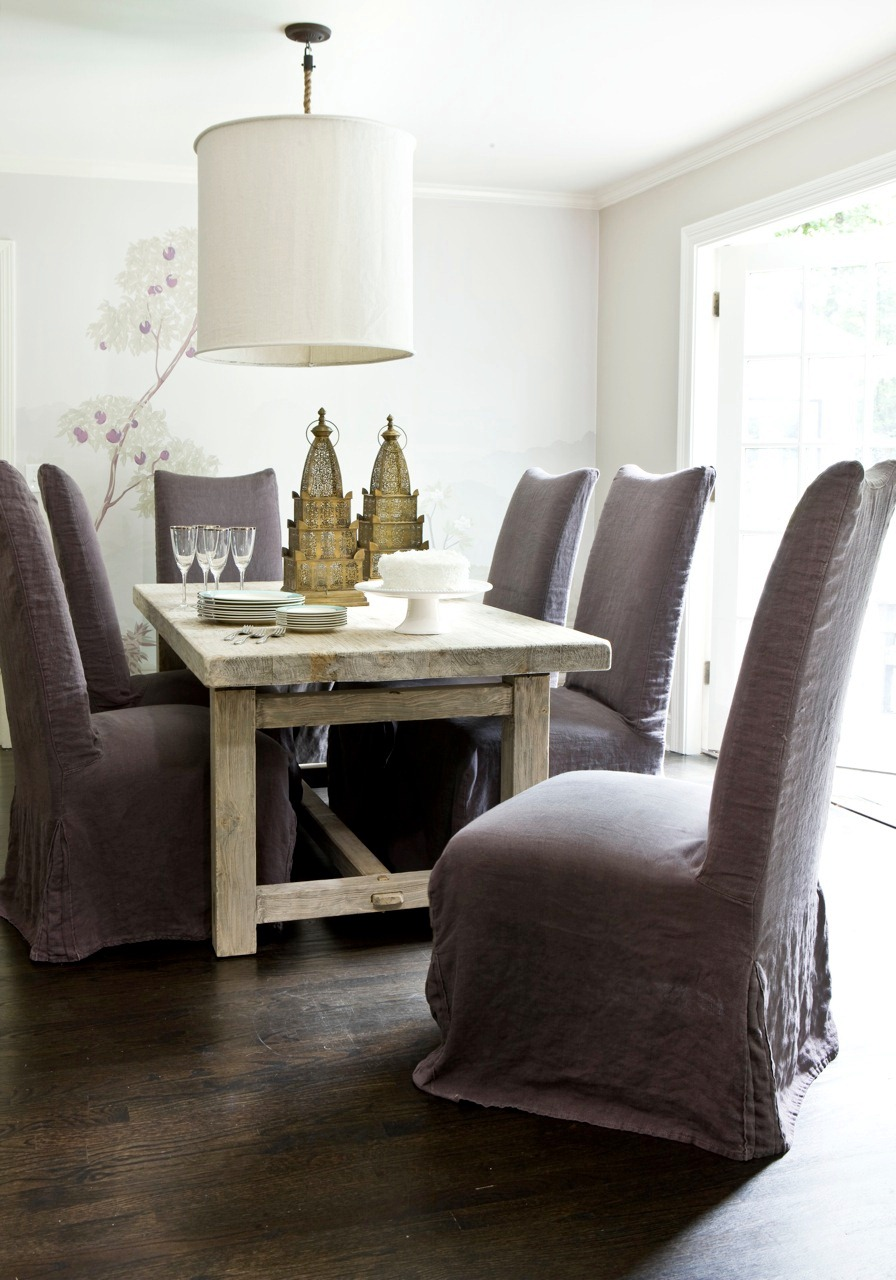 Formal dining room with light wood rough hewn table linen upholstered