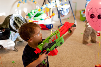 A two-year-old aiming a nerf gun at a balloon