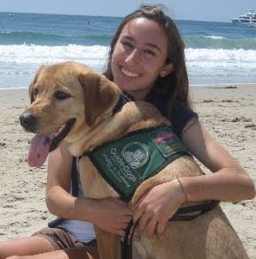 Elizabeth Kaufman with yellow Lab puppy at beach