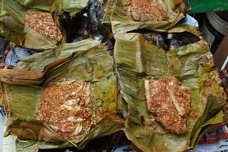Spicy fish wrapped up in banana leaves (at the market)