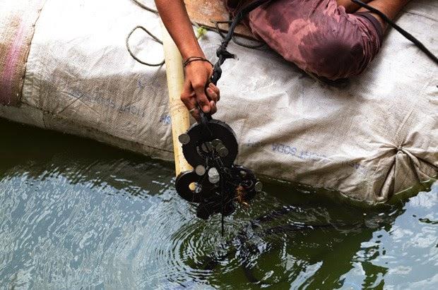 Jovem caça moedas em rio usando ímã e bote improvisado na Índia