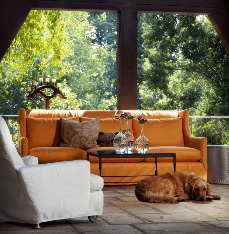 White slipcover chair and slicover orange sofa on a screened coastal porch