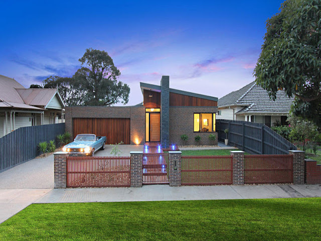Picture of small family home with blue Ford Mustang in front