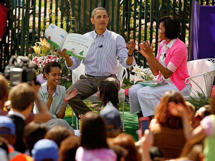 president barack obama reading a children's book on the white house lawn
