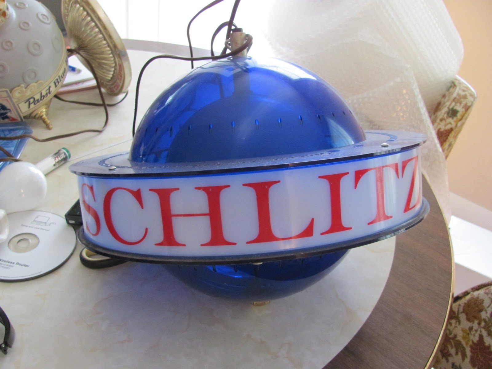 Blue spinning globe light with the Schlitz logo