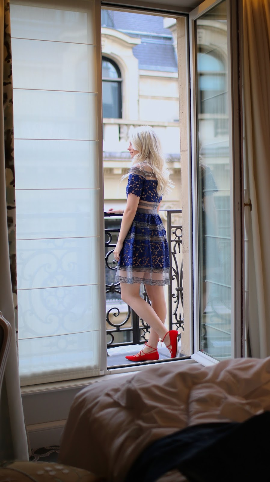 blonde women stands on hotel balcony in paris in beautiful blue lace dress and red shoes
