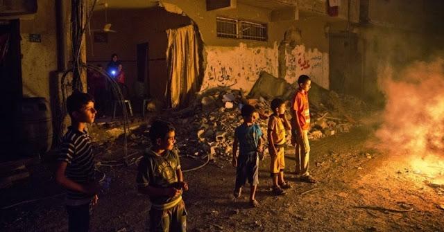 Crianças palestinas brincam em torno de uma fogueira acesa em uma rua no bairro de Shejahiya, em Gaza.