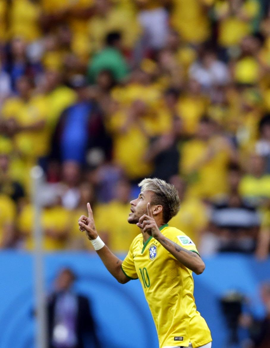 Brazil's Neymar celebrates scoring the opening goal during the group A World Cup soccer match between Cameroon and Brazil at the Estadio Nacional in Brasilia, Brazil, Monday, June 23, 2014.