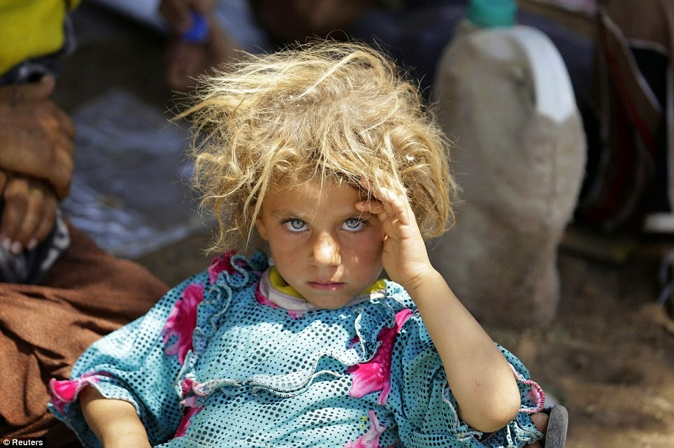 A GIRL FROM THE MINORITY YAZIDI SECT RESTS AT THE IRAQI-SYRIAN BORDER CROSSING IN FISHKHABOUR, DOHUK PROVINCE AFTER FLEEING ISLA - 29 Breathtaking Photographs of The Human Race