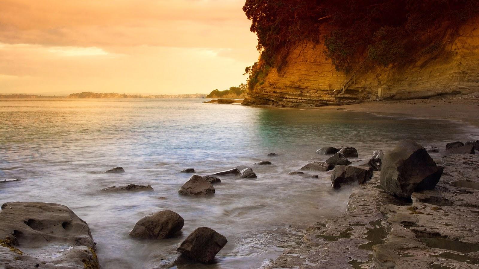 ... fotografía de una playa muy bella con algunas rocas en la orilla