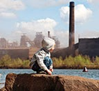 Child looking at smokestack (Credit: unep.org)