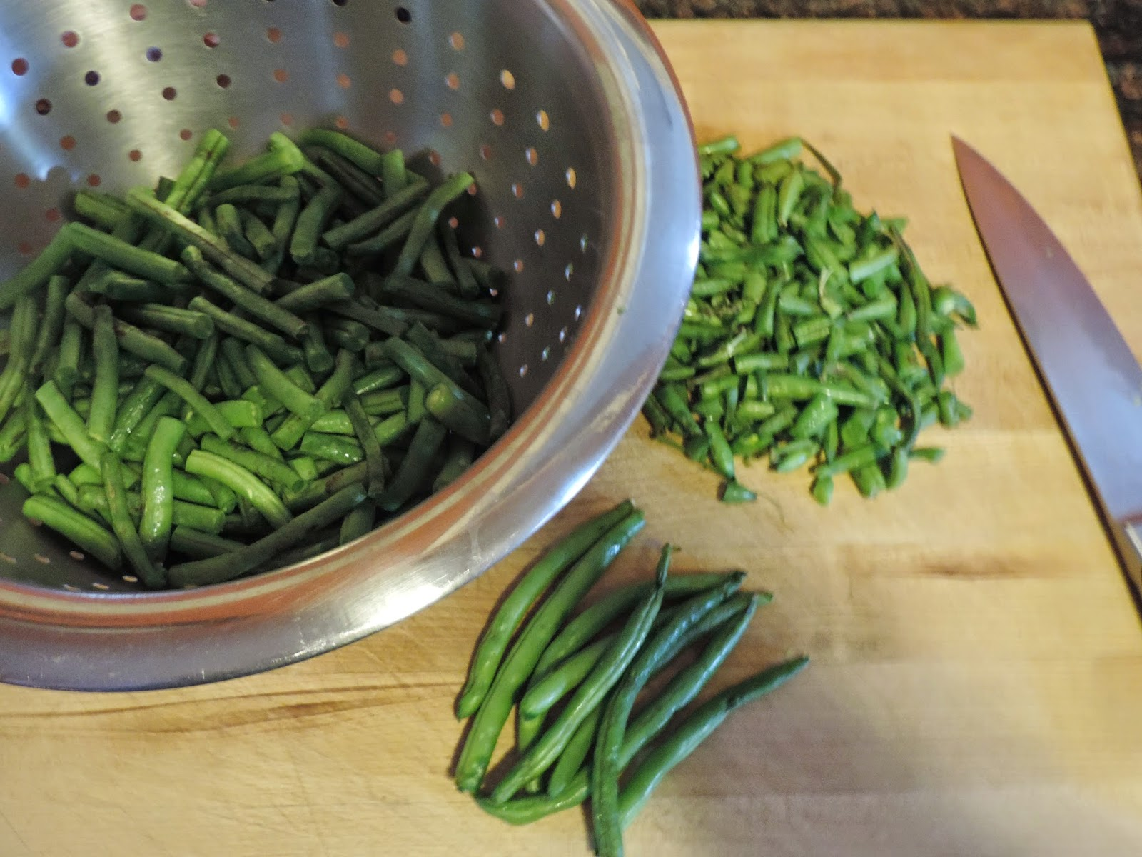 The green beans being trimmed and put in a strainer.
