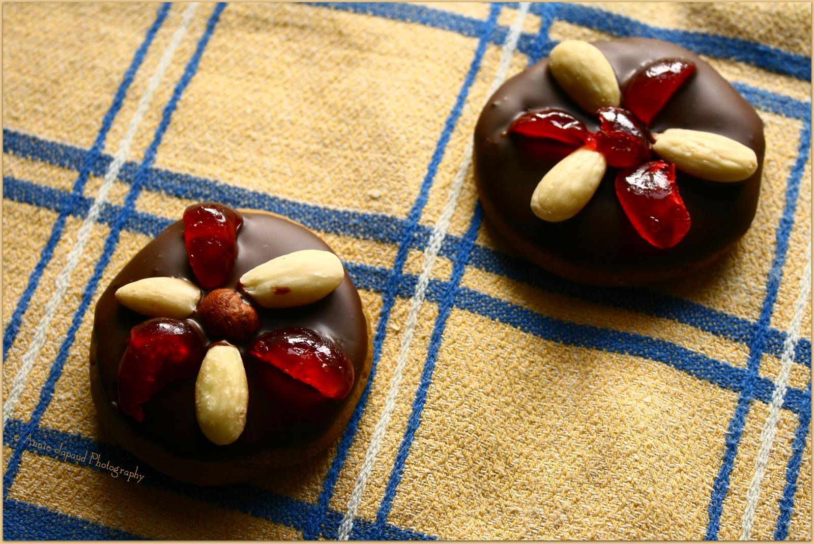 ginger snap cookies decorated with almonds and cherries