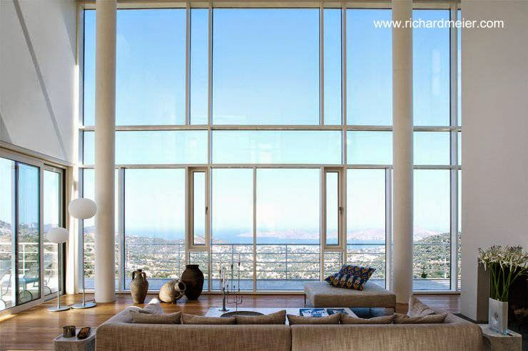 Sala de estar con amplia abertura de doble altura con vidrios