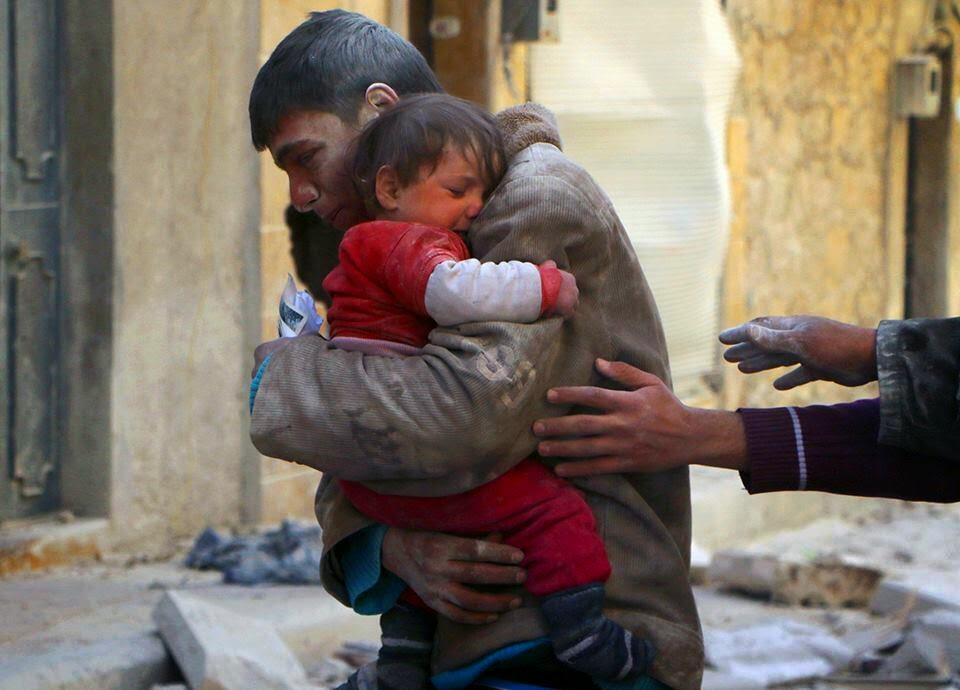 A BOY RESCUES HIS SISTER FROM UNDERNEATH THE RUBBLE OF THEIR HOME IN SYRIA - 29 Breathtaking Photographs of The Human Race