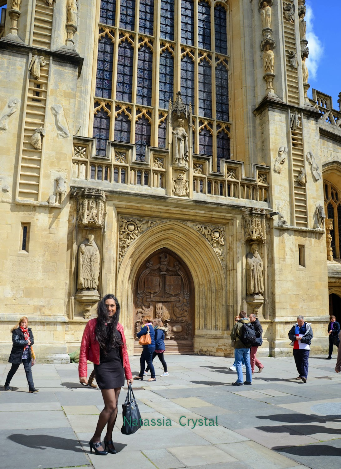 Standing in front of Abbey Church in a black dress, red leather jacket and black high heels