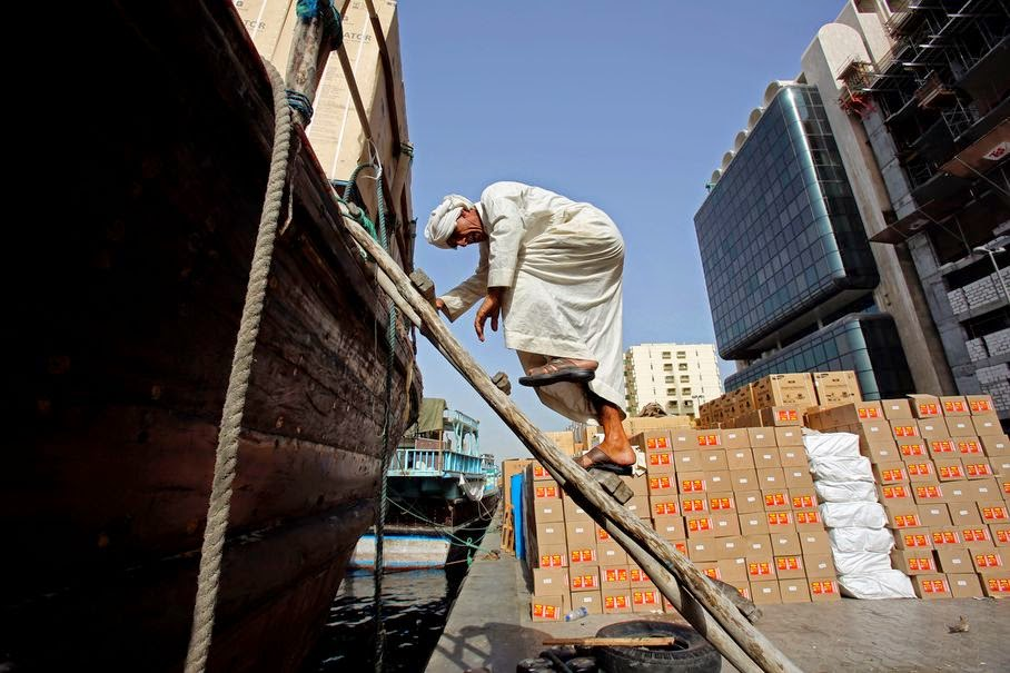 In this Tuesday, May 13, 2014 photo, an Iranian sailor climbs down a ladder from his dhow for uploading goods at the creek in Dubai, United Arab Emirates. The Creek has constantly been an important harbor for small and medium size dhows which sail to the ports of the Persian Gulf region, the countries of the Indian subcontinent and East Africa, loaded with different goods which are re-exported to these various regions.
