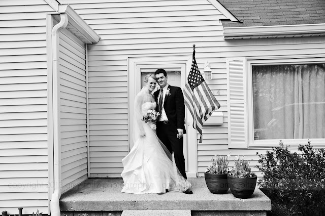 bride and groom in front of their home
