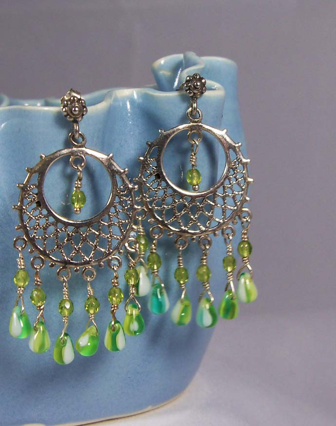 A silver pair of handmade earrings with green beads, created by Cynthia from Antiquity Travelers