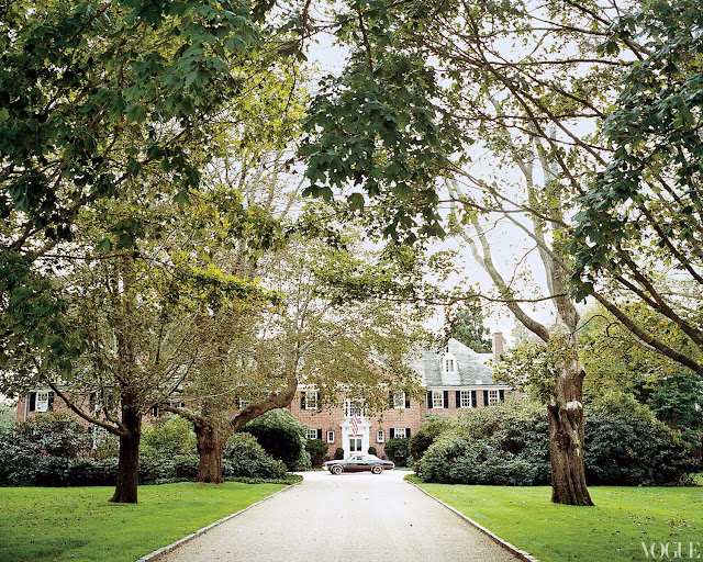 exterior of brick Georgian style house with long driveway surrounded by allee trees