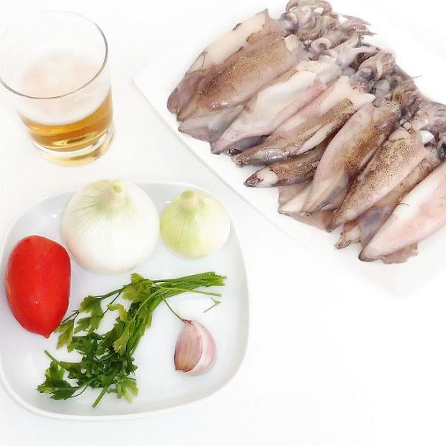 Calamares, cebollas, tomate, ajo, perejil y cerveza sobre fondo blanco