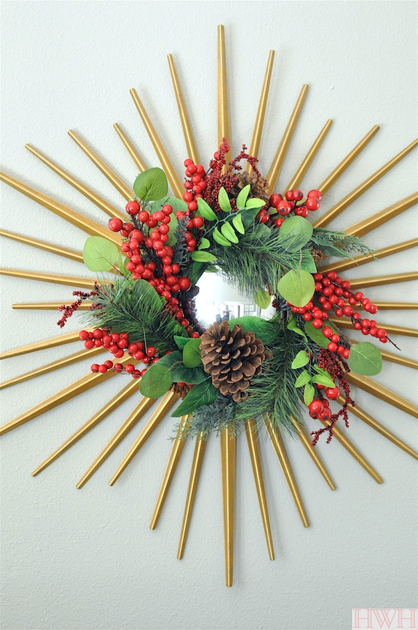 Festive holiday decor- berry and pinecone wreath hung from a gold starburst mirror| Honey We're Home