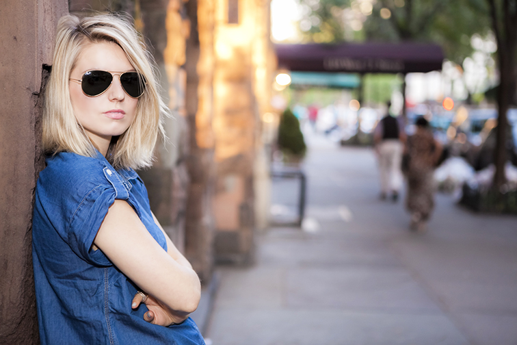 Messy blond hair, deep hair part and flip, golden hour, New York City, Ray-Ban Aviator sunglasses, denim tunic