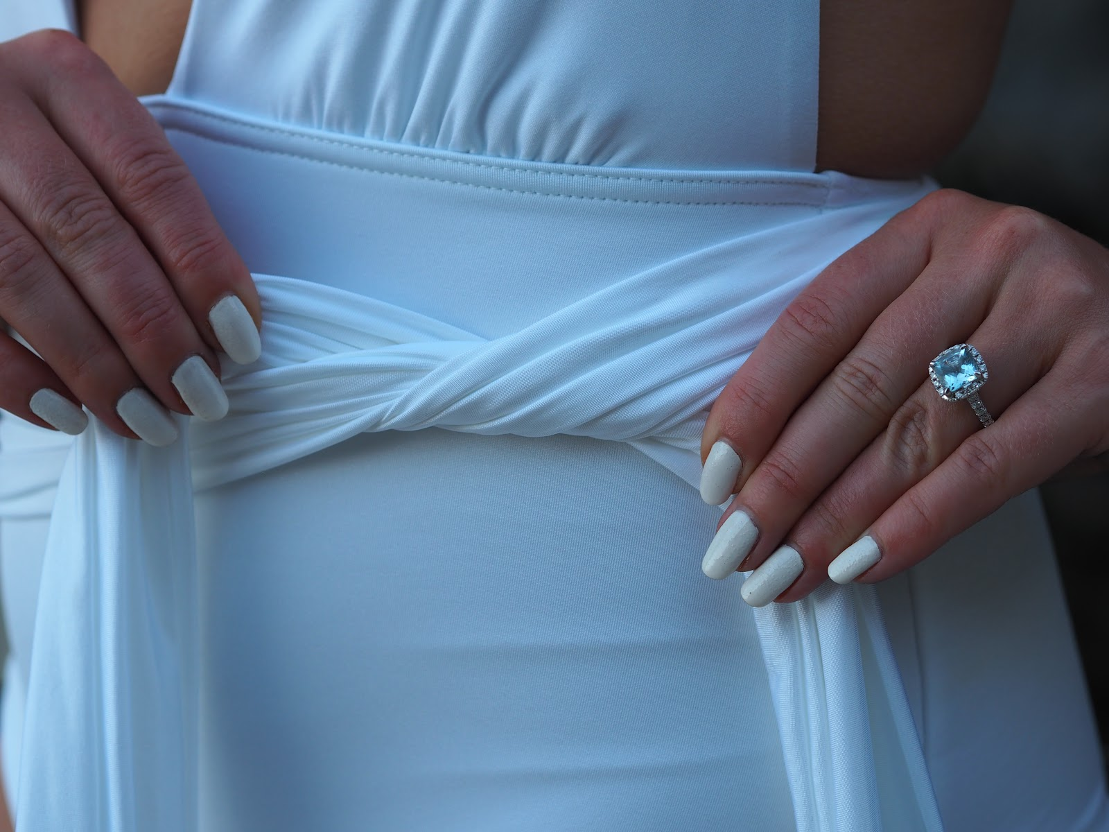 white fingernails tying white swimsuit bow with beautiful engagement ring