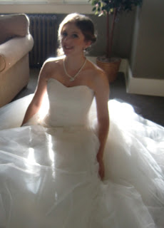 Kathryn sitting on the floor surrounded by her wedding dress.  Photo by Patricia Stimac