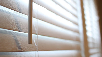 While faux wood window blinds block out the morning sun, the further window is opened to let fresh air and light in